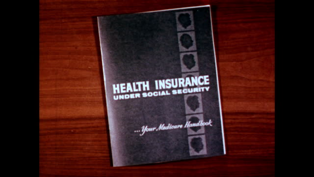 / booklet entitled 'health insurance under social security' sitting on a table / hand flips through the pages and closes the manual / medicare... - 社会保障点の映像素材/bロール