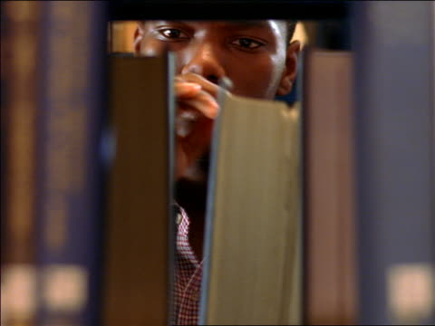 vídeos de stock e filmes b-roll de books in bookshelf removed reveal black male student examining books / boston, ma - biblioteca
