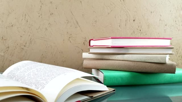 books stack and open book on glass desk. - hardcover book stock videos and b-roll footage