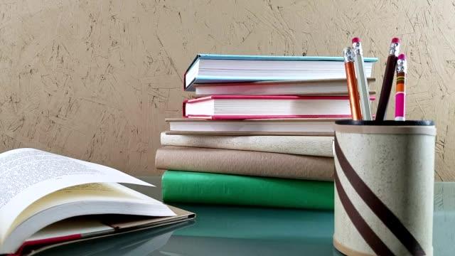 Bücher-Stapel und offenes Buch auf Glasschreibtisch.