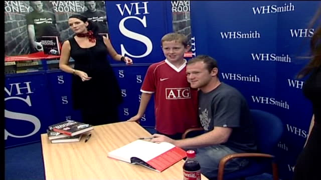 wayne rooney's autobiography; moyes to take legal action; manchester: the trafford centre: whsmith: int wayne rooney posing with young fan at book... - autobiography stock videos & royalty-free footage