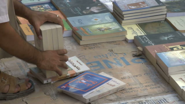 bookseller aligning and arranging books at a market / baghdad, iraq - libro in brossura video stock e b–roll