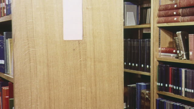 1965 PAN Bookshelves in the library and a student reading a book at Sussex University / Brighton, England , United Kingdom