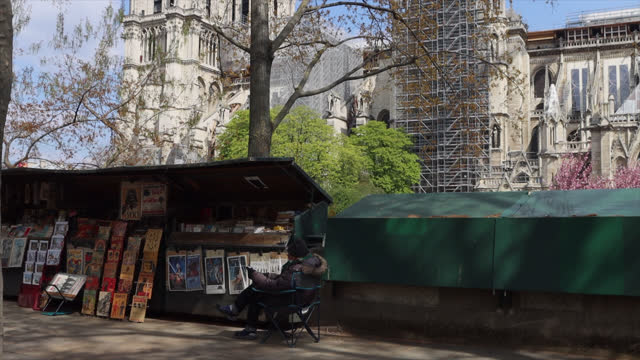 bookstore and people on the quays next to notre-dame de paris cathedral are seen almost two years after the fire that ravaged the iconic monument on... - 14 15 years stock videos & royalty-free footage