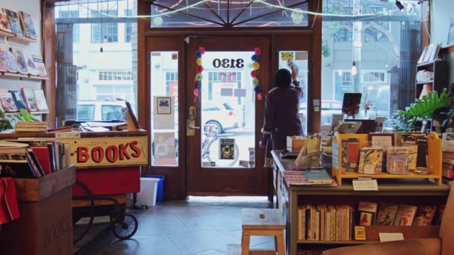 bookstore worker flipping sign to open - shop stock videos & royalty-free footage