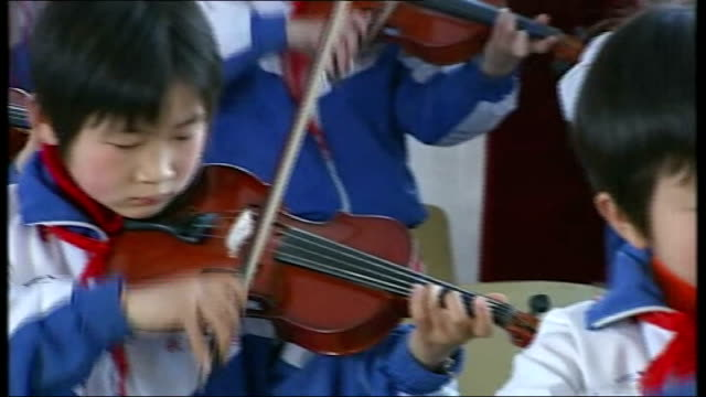 vídeos de stock e filmes b-roll de boom in classical music; china: xiqiao: int children in tracksuits practicing violin in class sot - fato de treino