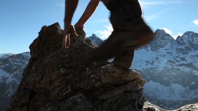 Boom past hands as mountaineer ascends narrow ridge, mtns