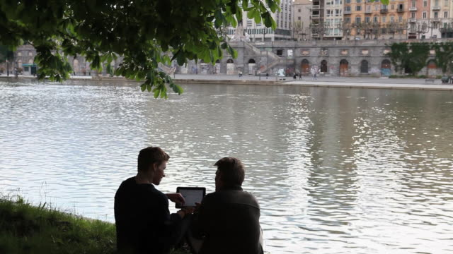 Boom shot as father and son stop beside river to look at digital tablet