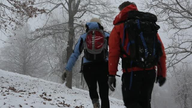 vídeos de stock, filmes e b-roll de boom shot of couple hiking in snowstorm - mitten