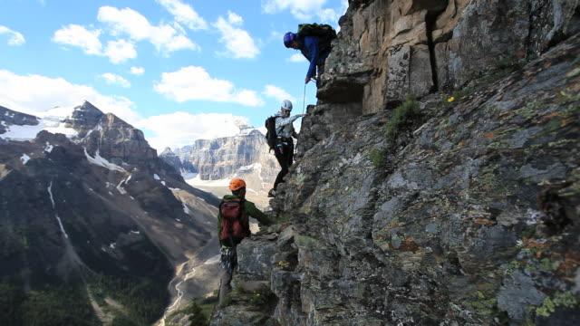 boom shot of three mountaineers climbing steep, man assists teammate - bergsteigen stock-videos und b-roll-filmmaterial