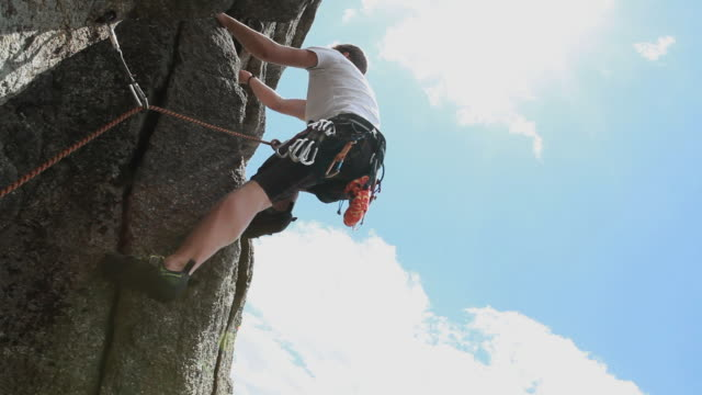 boom upward to teenager leading rock climb, clipping protection - männlicher teenager allein stock-videos und b-roll-filmmaterial