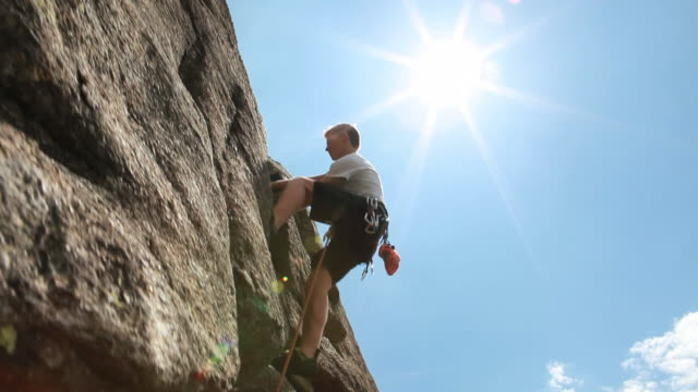 vídeos de stock e filmes b-roll de boom upward to teenager leading rock climb, clipping protection - corda de trepar