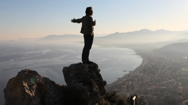 boom upwards as man climbs rock above sea, sunset - hand on hip stock videos & royalty-free footage