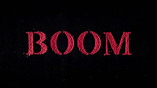 Boom written in red powder exploding in slow motion.