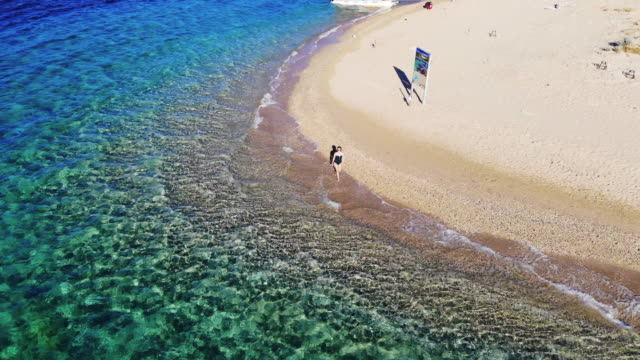 vídeos de stock e filmes b-roll de boomerang drone selfie of a woman in idyllic beach with emerald colors in greek island. - bumerangue