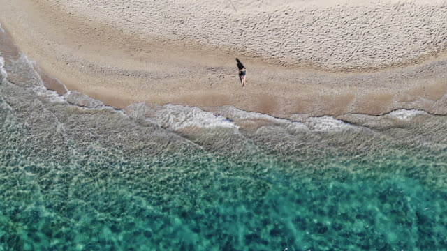 boomerang drone selfie of a woman in idyllic beach with emerald colors in greek island. - ブーメラン点の映像素材/bロール