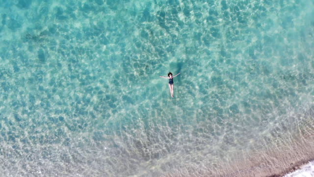 boomerang drone selfie of a woman in idyllic beach with emerald colors in greek island. - zoom out stock-videos und b-roll-filmmaterial