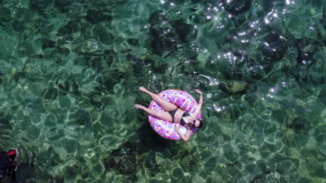 boomerang drone selfie of happy woman in inflatable donuts floating in the sea. - kvinnor i 30 årsåldern bildbanksvideor och videomaterial från bakom kulisserna