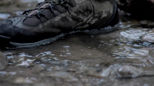 vídeos de stock e filmes b-roll de c/u boot footstep on stream - pegada