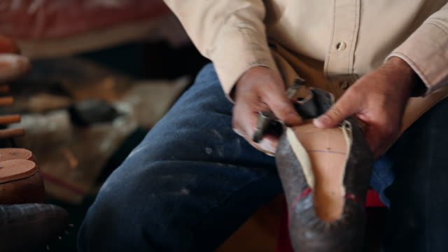 MS TU boot maker stretching vamp over sole of cowboy boot