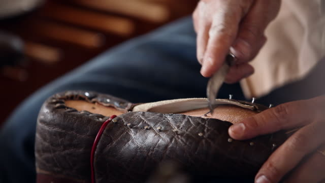 CU PAN boot maker trimming excess leather from sole of cowboy boots