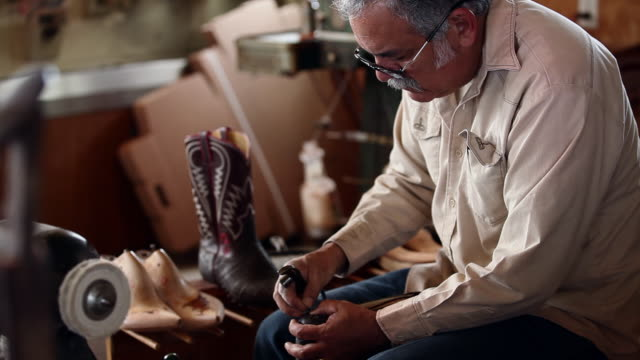 ms td tu boot maker using tool to stretch leather and place tacks in sole of cowboy boot - leather shoe stock videos and b-roll footage