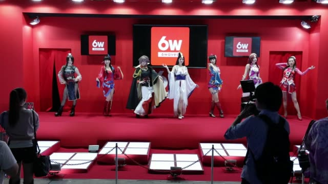 vídeos de stock, filmes e b-roll de booth attendants dressed in cosplay pose for photographs in the six waves inc. booth at the tokyo game show 2017 at makuhari messe in chiba, japan,... - game show