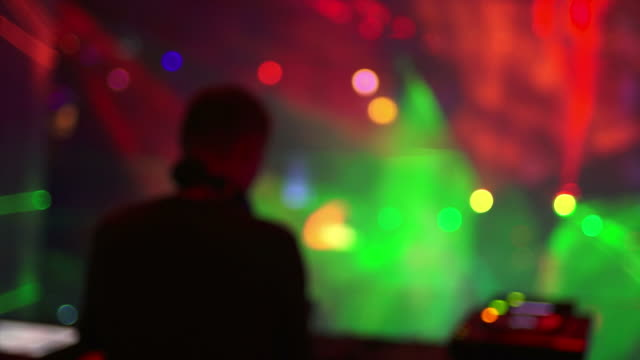 hd dj booth in front of disco lights (defocused) - techno music stock videos & royalty-free footage