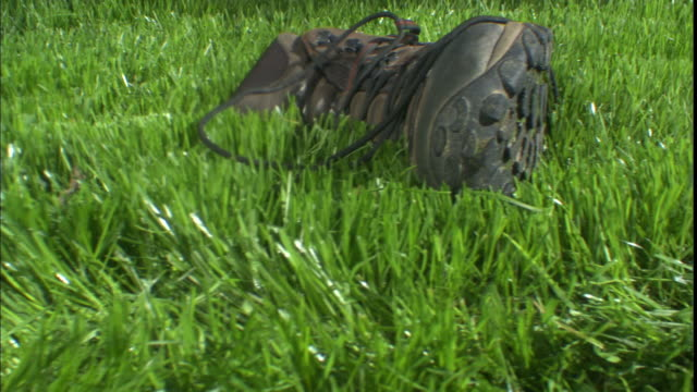 boots and socks lie in the grass next to man standing barefoot. - toe stock videos & royalty-free footage