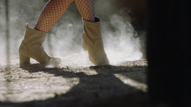 CU SLO MO. Boots kick and stomp up dust on rustic barn floor.