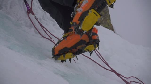 boots with crampons climb ice wall on a ice waterfull