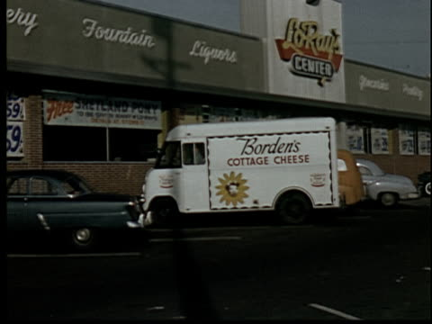 vídeos de stock, filmes e b-roll de 1955 ws borden's cottage cheese truck parking in front of supermarket/ driver loading shipment onto hand truck - 1950