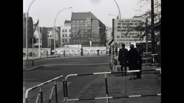 Border crossing at the Berlin Wall cars leaving Western Berlin into the East soldiers Allied Check Point of the American Sector in different shots...