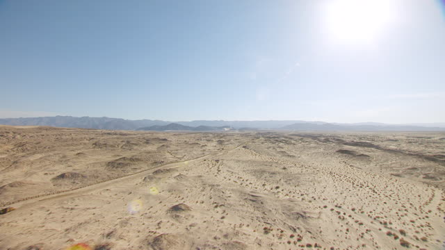 WS AERIAL POV Border fence between California and Mexico cutting across desert valley with foothills and mountain ranges in distance / California, United States