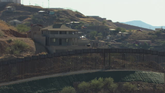 MS AERIAL Border fence in front of house on Mexico side / Nogales, Arizona, United States