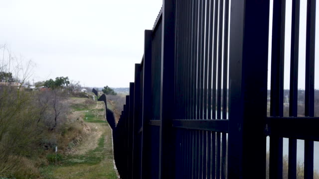 border fence is seen near the rio grande which marks the boundary between mexico and the united states on february 09, 2019 in eagle pass, texas. the... - 国境の壁点の映像素材/bロール