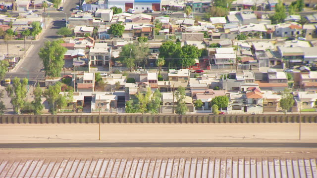 WS AERIAL POV Border fence passing between cultivated California farmland in foreground with residences of Mexicali Mexico in background / Calexico, California, United States