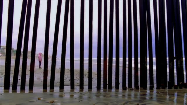 vídeos de stock e filmes b-roll de ms, pan, border fence usa/mexico and beach, san diego, california, usa - cerca