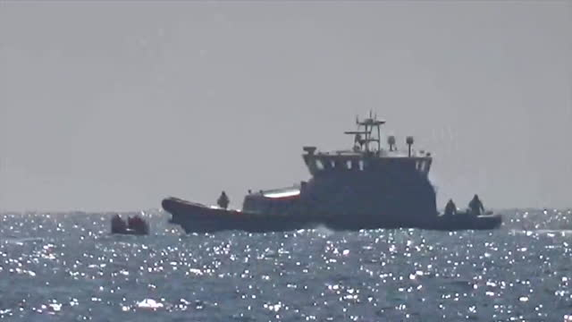 border force boat picking up migrant boat of asylum seekers off the coast of dover, kent - small boat stock videos & royalty-free footage