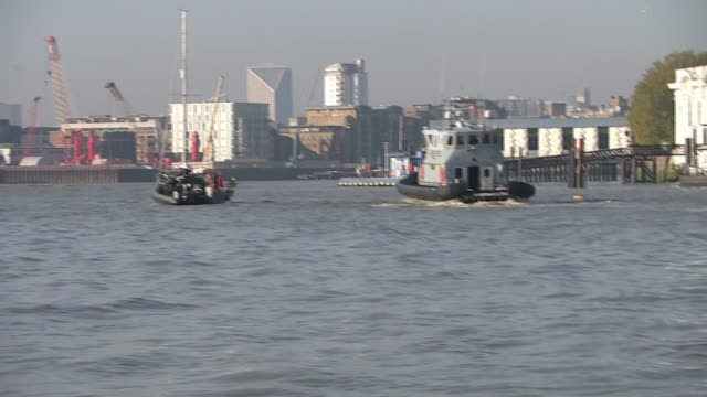 UK Border Force launches patrol boat on River Thames EXT Wide shot of Border Force boat and police boat approaching yacht Police officers climbing...