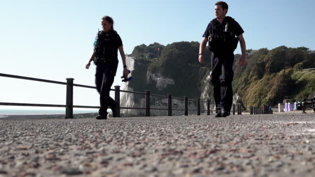 border force officers walk along a beachfront promenade, in front of the white cliffs of dover while patrolling the kent coast searching for migrant... - hügelkette stock-videos und b-roll-filmmaterial