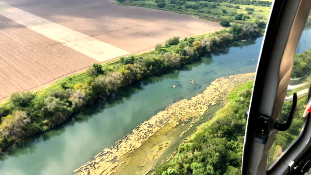 border patrol agent flies in a helicopter patrol over the rio grande and the u.s.-mexico border on november 7, 2018 in mission, texas. u.s. air and... - mcallen texas stock videos & royalty-free footage