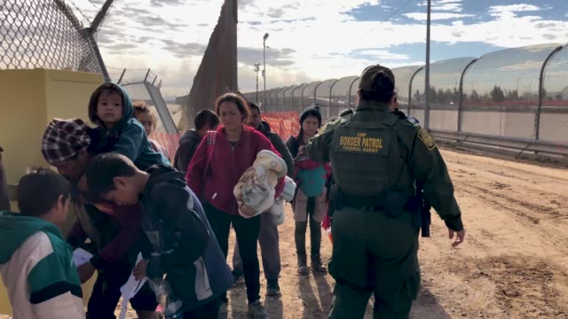 US Border Patrol agent speaks with Central American immigrants at the USMexico border fence on February 01 2019 in El Paso Texas The migrants were...