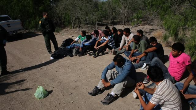 us border patrol agents detain a group of 16 immigrants from mexico and el salvador who had just crossed the rio grande river from mexico into texas... - deportation stock videos & royalty-free footage