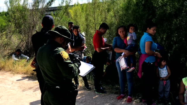 us border patrol agents take central american asylum seekers into custody on june 12 2018 near mcallen texas the families were then sent to a us... - 地理的境界点の映像素材/bロール