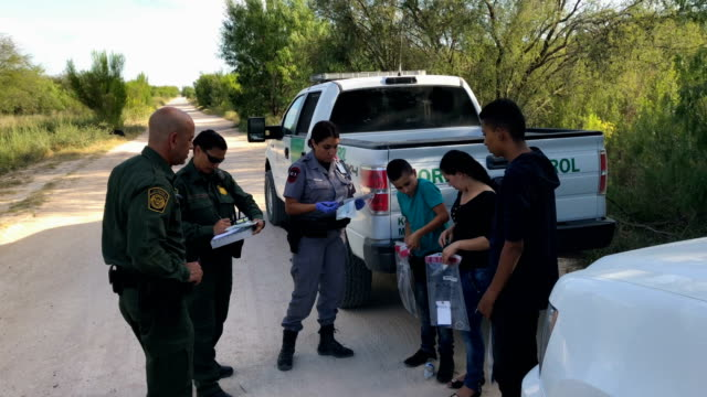 US Border Patrol agents take Central American asylum seekers into custody on June 12 2018 near McAllen Texas The families were then sent to a US...