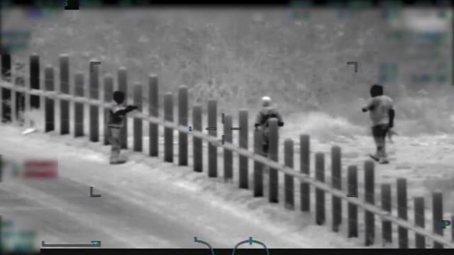 Border Patrol observe several men armed with rifles escort a mother and child to the international boundary west of Lukeville Arizona The armed men...