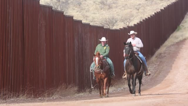 US Border Patrol ranch liaison Agent John Jackson rides with Arizona rancher Dan Bell on Bells ZZ Cattle Ranch on the border with Mexico Jackson...