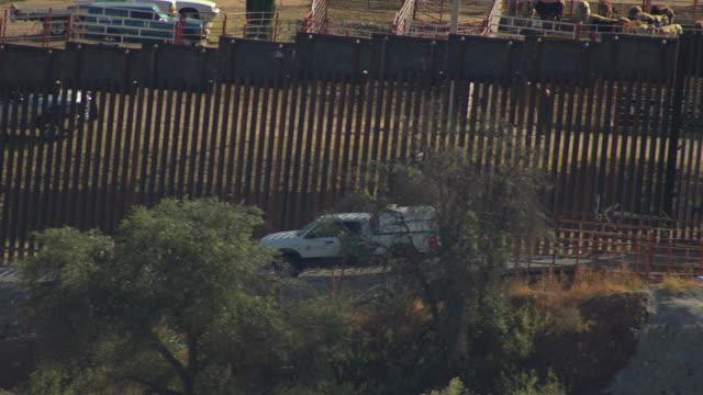 ms aerial zo border patrol truck driving along border fence / nogales, arizona, united states  - border patrol stock videos & royalty-free footage