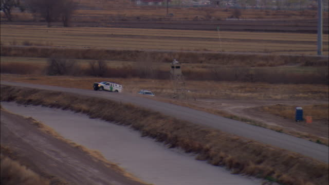 low aerial u.s. border patrol truck driving on road at us-mexican border, el paso, texas, usa - border patrol stock videos & royalty-free footage